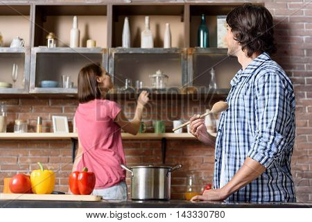 Joyful married couple is cooking together. Woman is looking for ingredient on shelf in kitchen. Man is standing near pot and holding wooden spoon. They are smiling