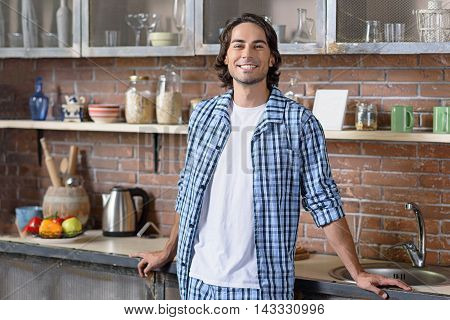 Happy young man is standing in kitchen and relaxing. He is looking at camera and smiling