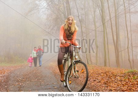 Happy active woman riding bike bicycle in fall autumn park. Glad young girl relaxing. Healthy lifestyle..