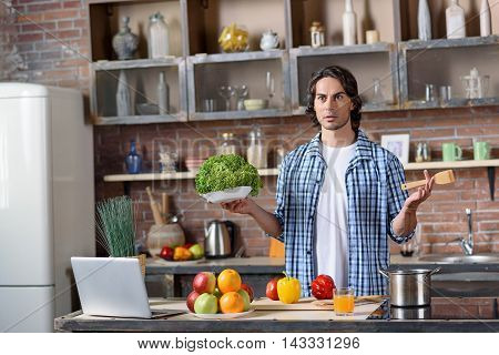 Puzzled young man is standing in kitchen and looking forward with shock. He does not know what to do. Guy is holding lettuce and wooden spoon