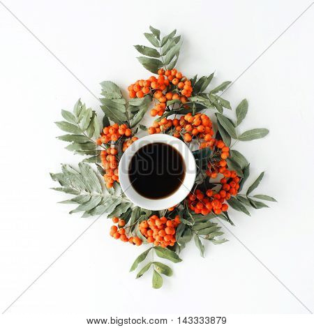 colourful bright pattern made of mountain ash berries and branches with coffee cup.