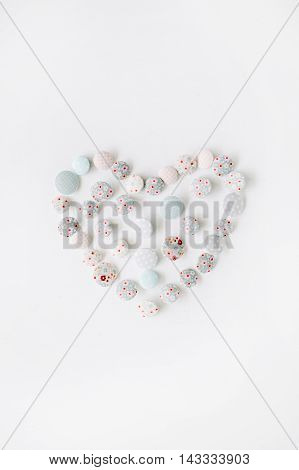 Heart symbol made of colorful buttons on white background.