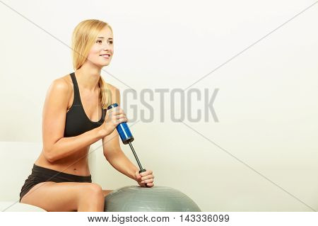 Sport training gym and lifestyle concept. Young attractive slim woman in sportswear with air pump inflating fit ball fitness exercise