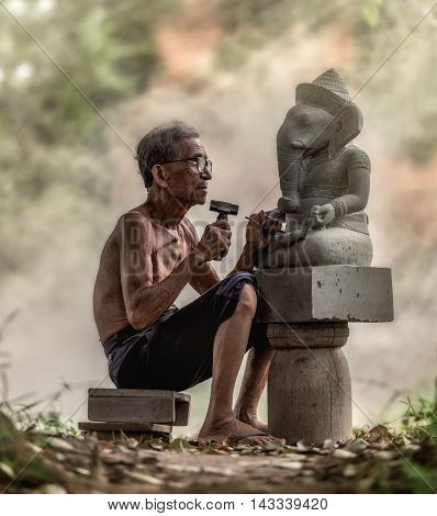Senior sculptors work on his sculpture in his workshop, Thailand