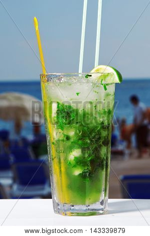 A Glass Of Mojito Cocktail With Mint On Beach And Sky Background