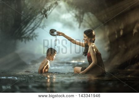 Sister and brother bathing in cascade Thailand