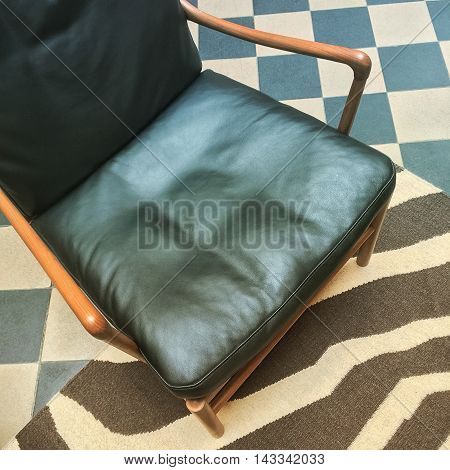 Close-up of leather armchair in retro style interior.