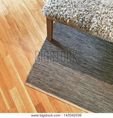 Scandinavian style interior with sheepskin bench gray rug and wooden floor.