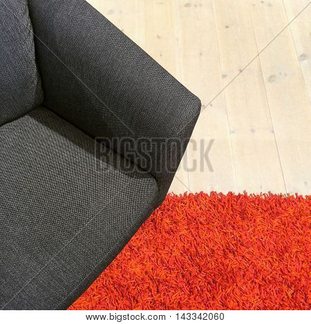 Gray textile armchair on red carpet. Contemporary style furniture.
