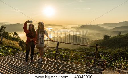 Woman taking photo with smartphone at mountain peakvintage effect