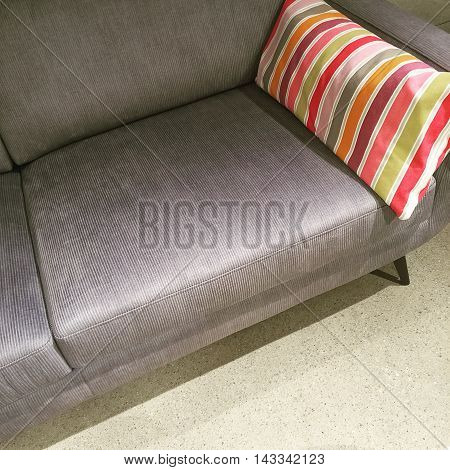 Gray sofa with colorful striped cushion on concrete floor.