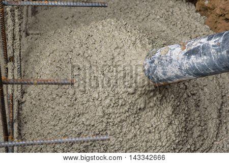 Concrete pumping hose filling a foundation hole