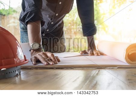 Image of engineer checking blue print on site