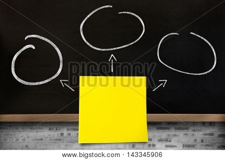 Close-up of yellow adhesive note against blackboard on wall