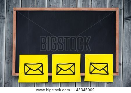 Digital composite image of yellow adhesive paper against blackboard with copy space on wooden board