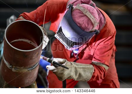 Pipe welding Worker with protective mask in factory