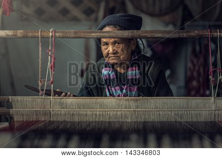 Old women demonstrate to procedure of making Thai Silk weaving