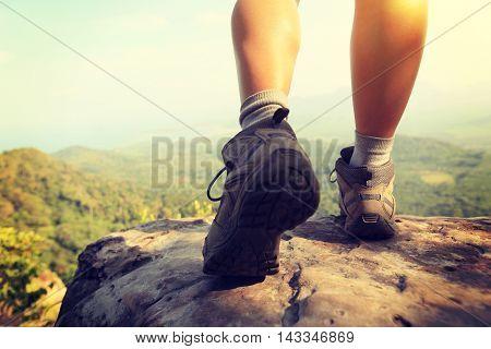 hiker legs climbing at mountain peak rock