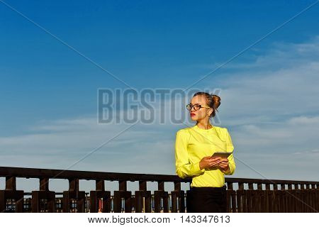 Girl waiting for a letter by e-mail outdoors. Business woman at work. Correspondence. Wireless technologies.