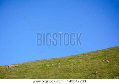 Moon In Blue Sky Above Mountain