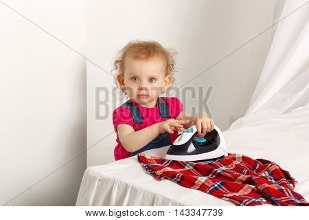 Nice little girl with iron to iron plaid shirt. Mom's helper. Household chores. Steaming folds.