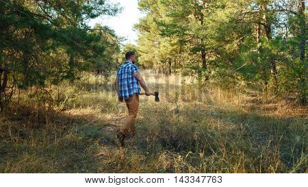 Lumberjack is in the woods holding the ax. A man in a plaid shirt. Hiking.