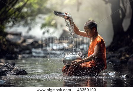 Novice Monk washing monk's alms bowl at creek in Thailand