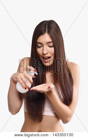 Joyful girl is holding bottle of soap. She is squeezing liquid on palm and looking at it with surprise. Lady is standing and laughing. Isolated