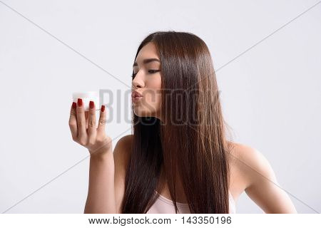 Carefree young woman is holding cream jar. She is standing and sending kiss to it with love. Isolated