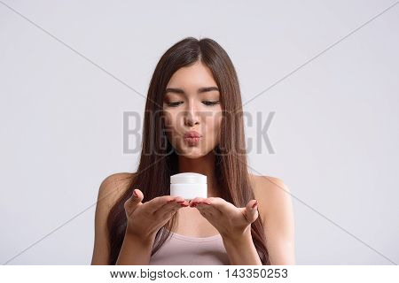 I love this cream. Cheerful girl is holding cream can and looking at it with satisfaction. She is sending air kiss to it. Isolated