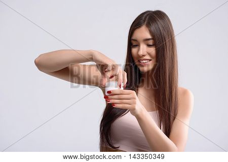 Carefree young woman is holding cream jar. She is standing and opening it with interest. Lady is laughing. Isolated