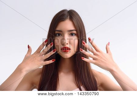 Voluptuous girl is showing her manicure. She is raising hands to face and looking forward with sensuality. Lady has red lips. Isolated