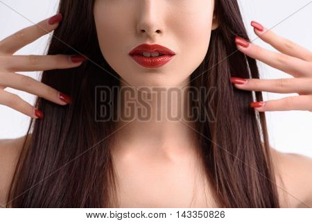 Close up of sensual young woman raising arms to hair with grace. She has red lips and fingernails