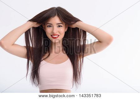 My hair is very smooth and healthy. Happy young woman is touching hair and smiling. She is looking at camera with satisfaction. Isolated