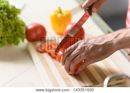 Close up of male arms chopping vegetable with knife in kitchen