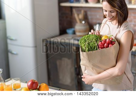 Joyful young woman is holding shopping packet with vegetables. She is standing in kitchen and smiling