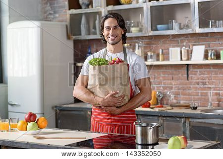 Happy young man is holding packet of healthy food. He is standing in kitchen and smiling