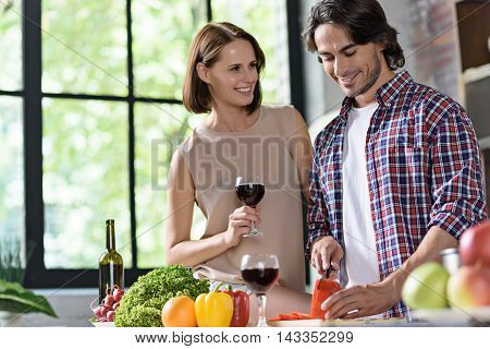 Happy married couple is standing in kitchen and smiling. Man is cooking healthy food for his wife. Woman is drinking wine and smiling