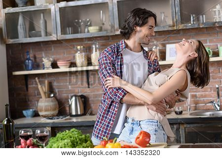 Pretty married couple is dancing and smiling in kitchen. Man is embracing woman is looking at her with love