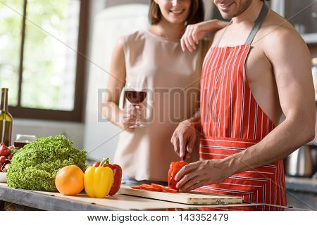 Happy woman watches her husband cooking romantic dinner. She is embracing him and smiling. Lady is holding wineglass. Man is cutting vegetable