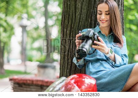 Skillful female photographer is sitting on bench in park near helmet. She is holding camera and looking at photos with interest. Woman is smiling