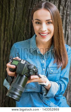 Happy young woman is sitting in park and holding camera. She is looking forward and smiling