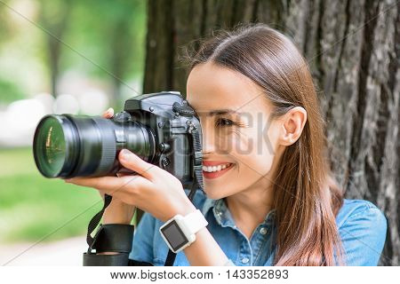 Joyful female photographer is taking shots of nature. She is holding camera near face and smiling