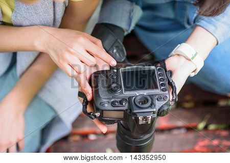 Close up of female hands holding camera. Photographer is showing photos to woman. They are sitting on bench