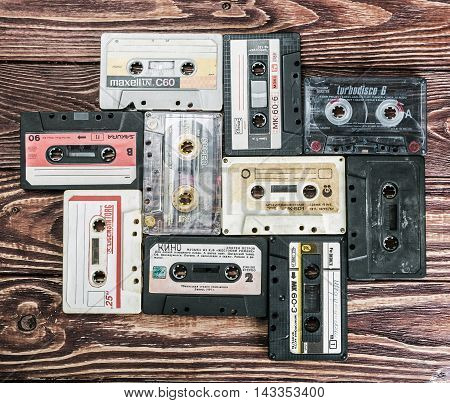 Moscow, RUSSIA - May 24, 2016: Old Cassette tapes over textured wooden table. Cassette tapes of different firms Maxell, Sakura, Svema etc.