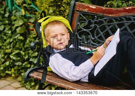 beautiful boy pre-schooler with a notebook in the Park . preschool education