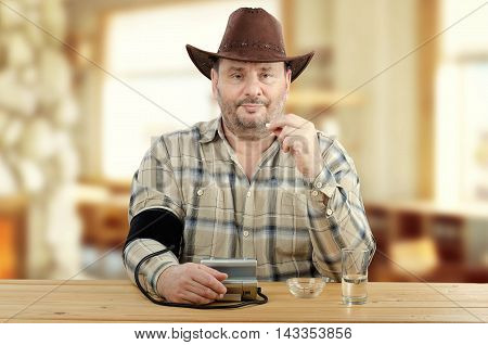 Mature cowboy checks his blood pressure before taking prescription tablets. Bearded man in checkered shirt, brown hat sits at wooden table, holds pill by left hand and looks directly at the camera. There are blood pressure gauge, glass water on the table
