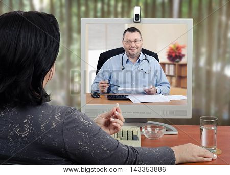 Female patient sits with her back to the camera and looks at virtual doctor in the monitor. Mature woman holds a pill by hand and ready to take it. Middle-aged bearded male doctor with glasses and a stethoscope reviews medical laboratory results with her