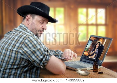 Mature cowboy sits at the wooden table tries to give intramuscular injection in his arm. However, man with black hat, checkered shirt holds the syringe incorrect. Virtual rural doctor in laptop monitor explains how to administer medication properly