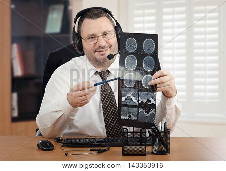 Mature male doctor in headset and glasses goes over brain x-rays results to virtual patient. Bearded handsome physician sits at office desk looks directly at the camera. There are keyboard, mouse and stethoscope on the desk